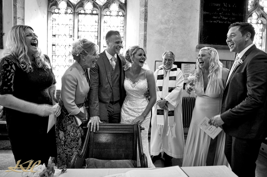 Fun Church Service, Laughing bridal party signing register, black & white, Kenny Hickey photography, Wedding Photographer Hever Castle