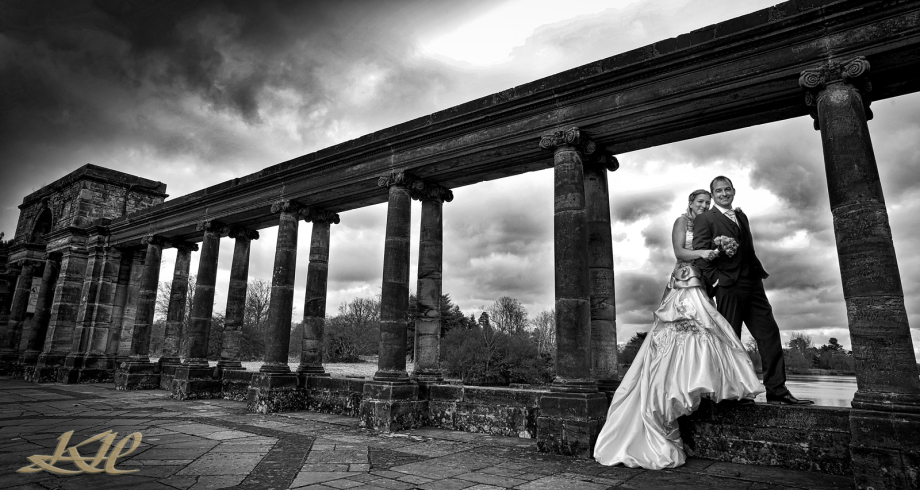 Bride & Groom posing on the Loggia at Hever Castle in black & white