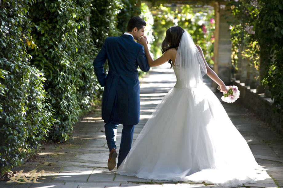 Italian Bride & Groom walking at Hever Castle kissing brides hand, Kenny Hickey Photography