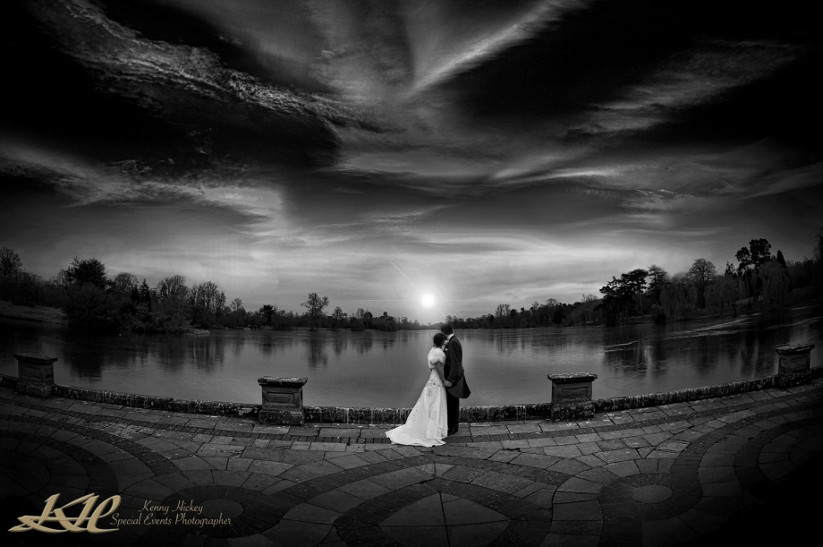 beutiful iconic black & white shot of bride and groom photo by the lake at Hever Castle & Gardens by sunset