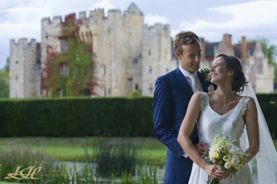 bride & groom posing with Hever Castle in the background