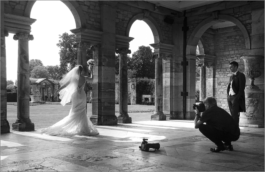 shot of Kenny at work photographing a bride on the Hever Castle Loggia in black & white