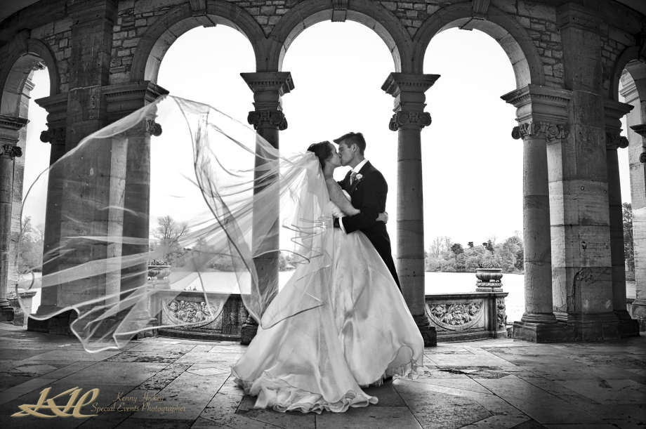 bride & groom at Hever Castle kissing with veil blowing in black & white