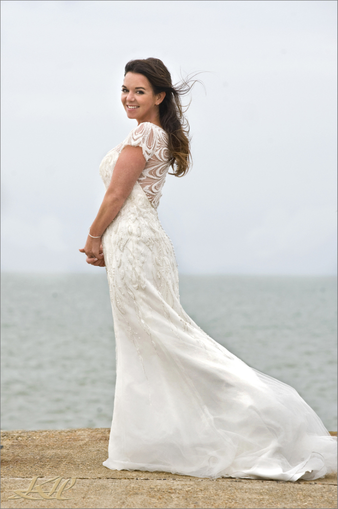 beautiful bride in wedding dress by the seaside at Whitstable with wind blowing