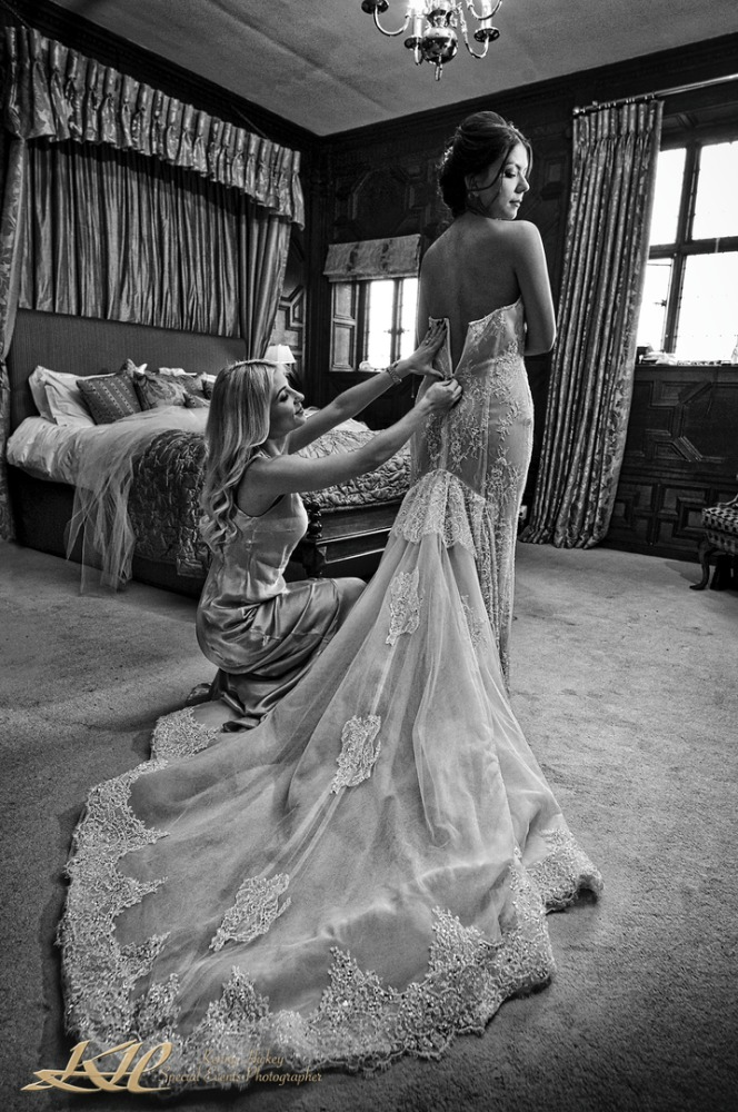 beautiful bride having wedding dress buttoned up at Hever Castle Tulip room in black & white