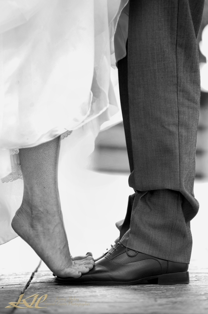 fun bride standing on grooms shoes in black & white