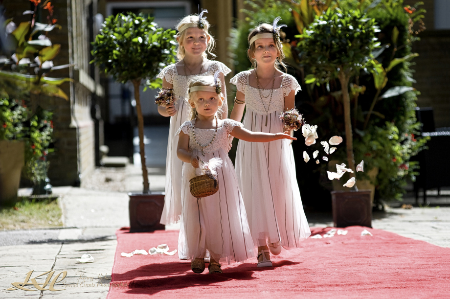 little bridesmaids walking the red carpet throwing white petals