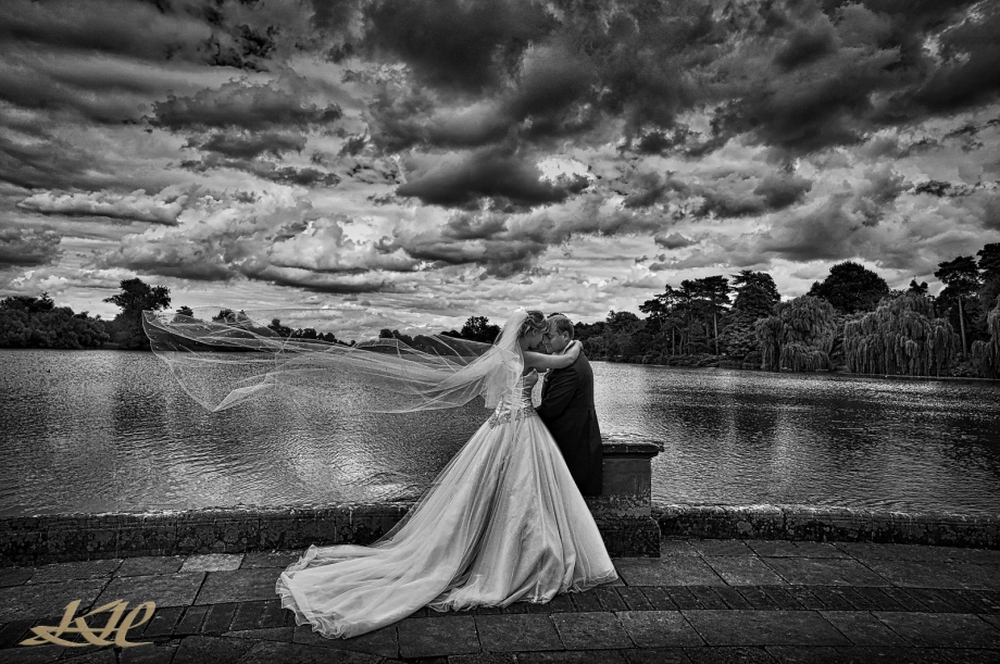 black & white of bride & groom romantic cuddle with flowing veil at never Castle lake