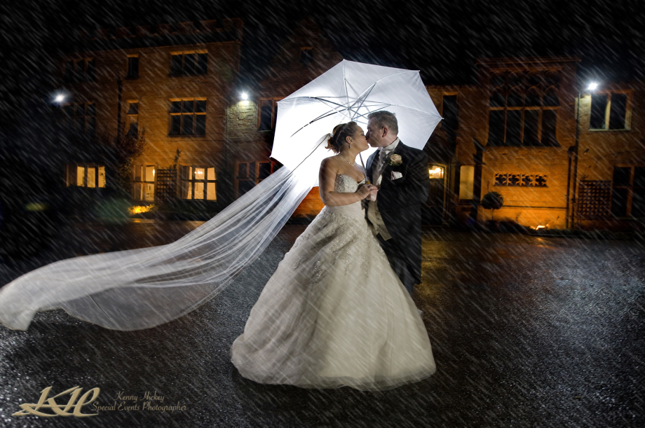 bride & groom in rain at night with white umbrella kissing