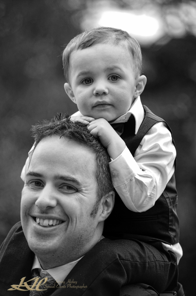 young page boy sitting on fathers shoulders in black & white