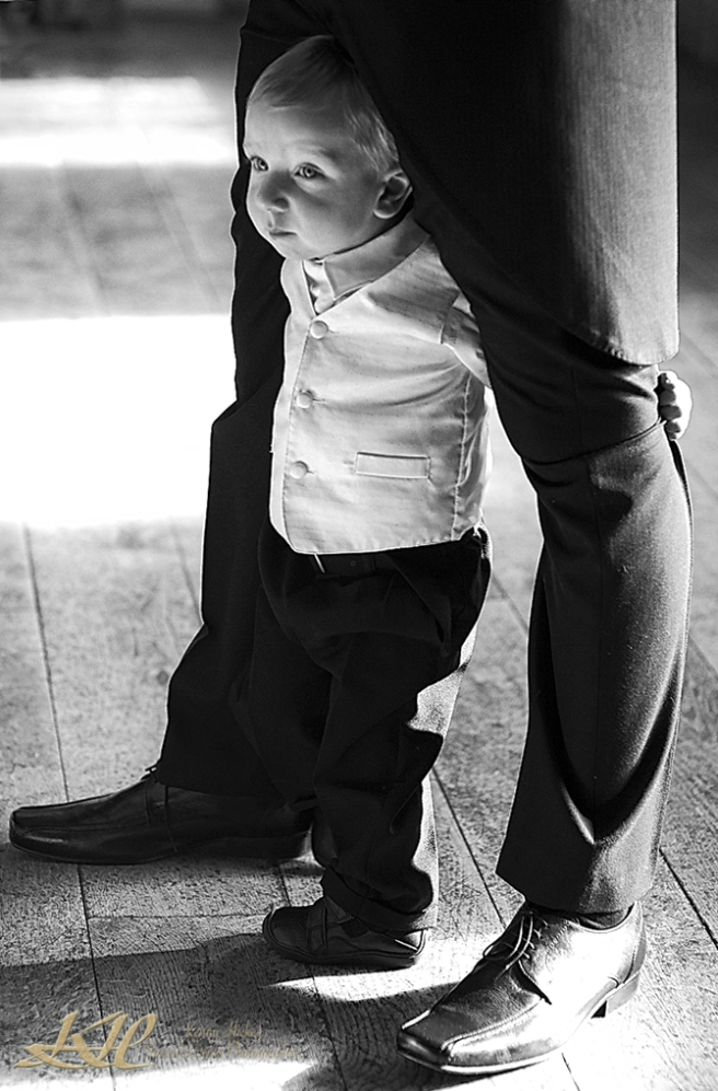 Young page boy peering through grooms legs in black & white