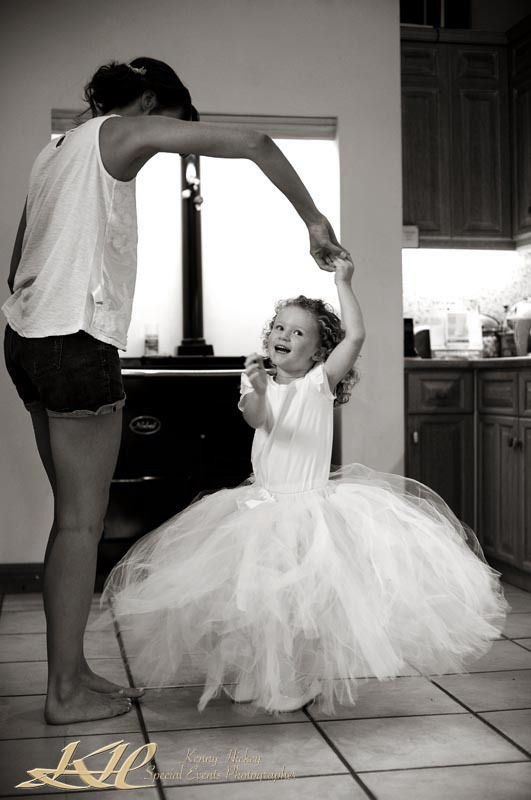 young flower girl dancing in kitchen with bride getting ready in black & white