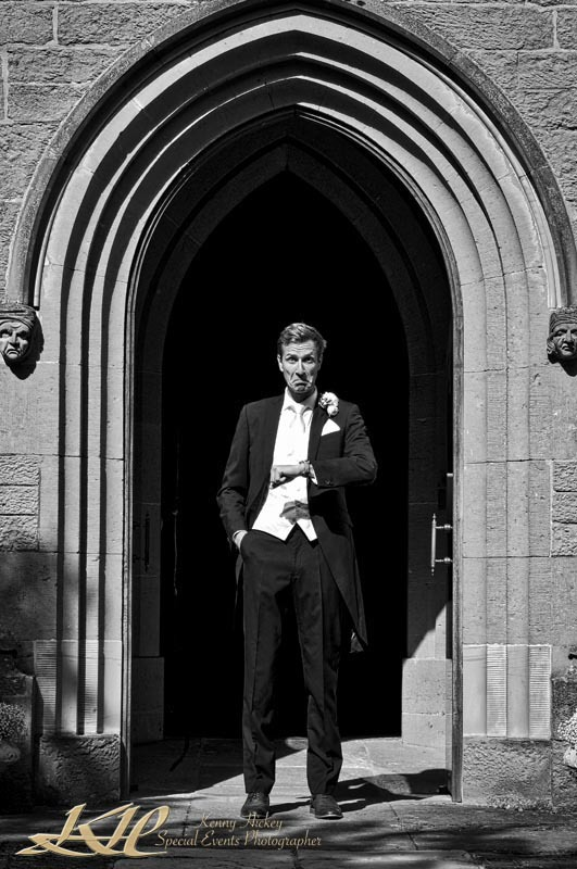 Groom looking at watch at church entrance fun black & white