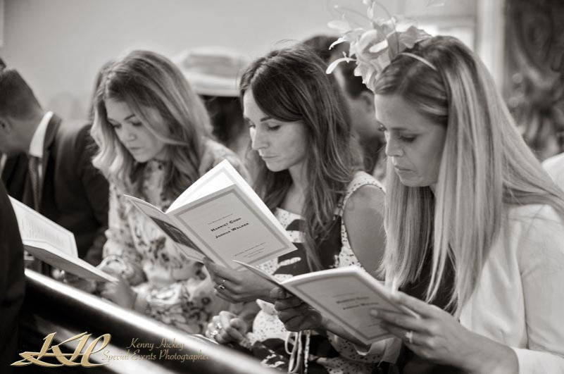 reportage wedding guests in church in black & white reading order of service