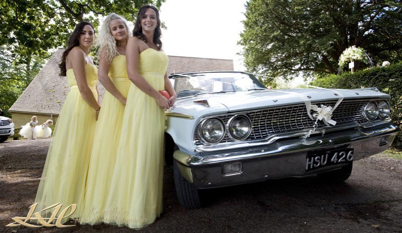 bridesmaids at church standing by large white cadillac