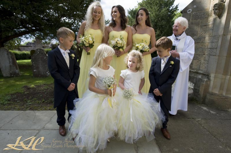 Page boys with bridesmaids at the church with the vicar