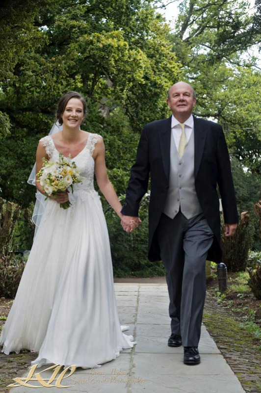 Bride walking to church with smiling father