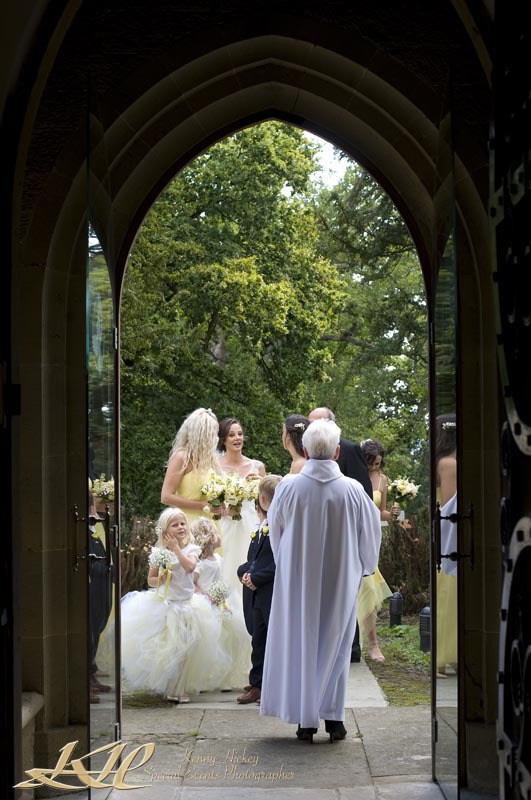 Bride and bridal party being greeting by the vicar at the church entrance