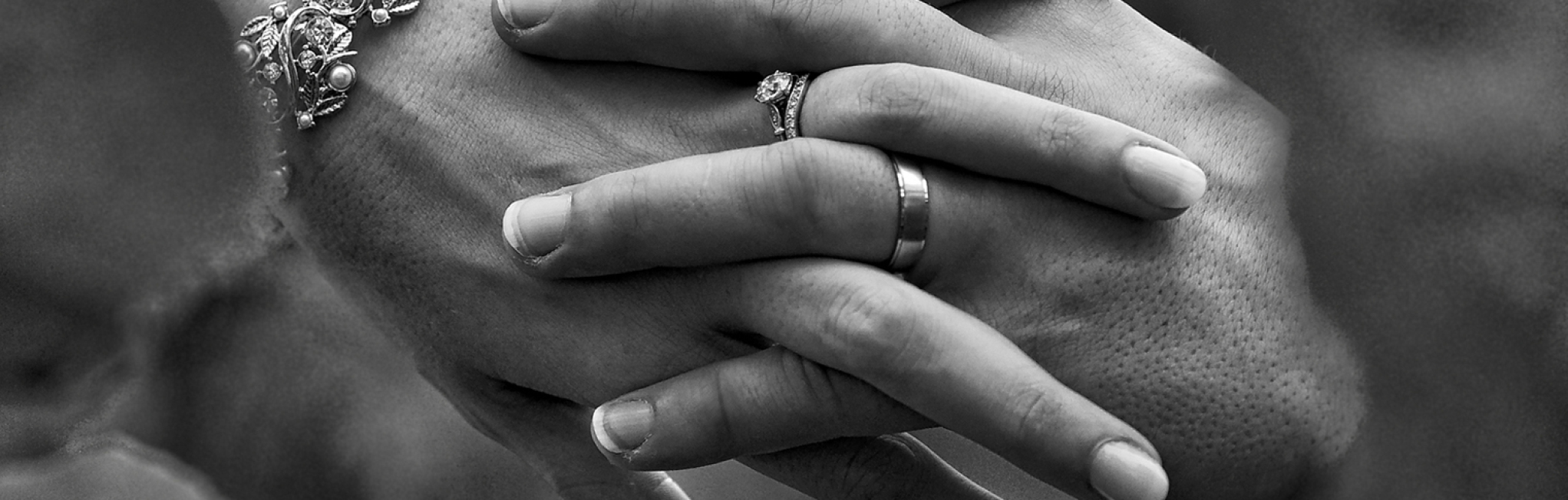 close up of bride & groom holding hands showing wedding rings in black & white