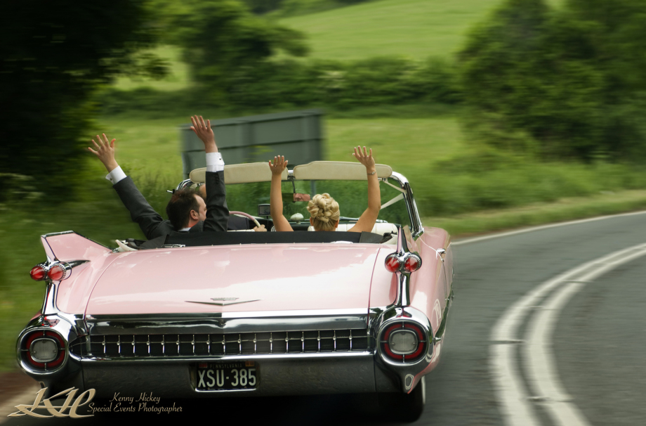 Fun shot of wedding couple holding hands up in pink cadillac