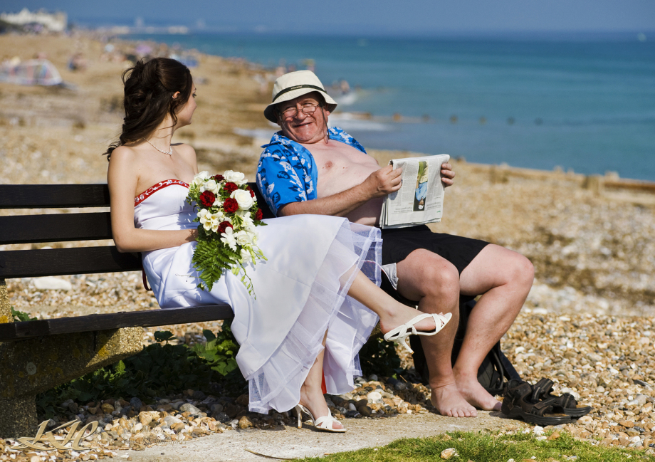 young beautiful bride sitting on seaside bench with old man in hat reading newspaper