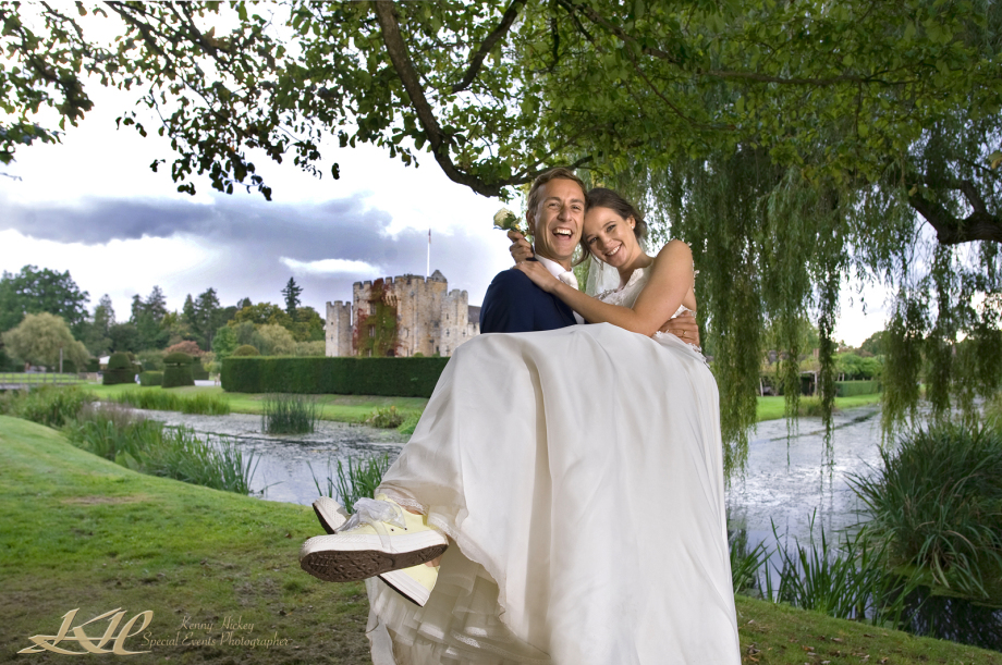 Laughing Groom carrying Bride wearing covers shoes at Hever Castle