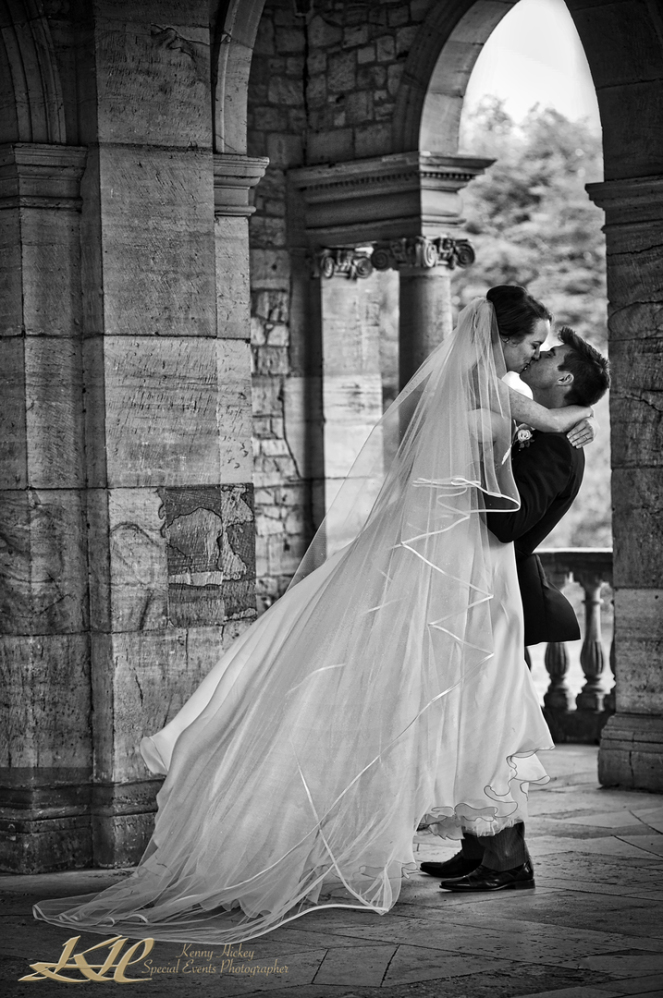 Groom picking up and kissing bride in long wedding dress in black & white at Hever Castle Loggia