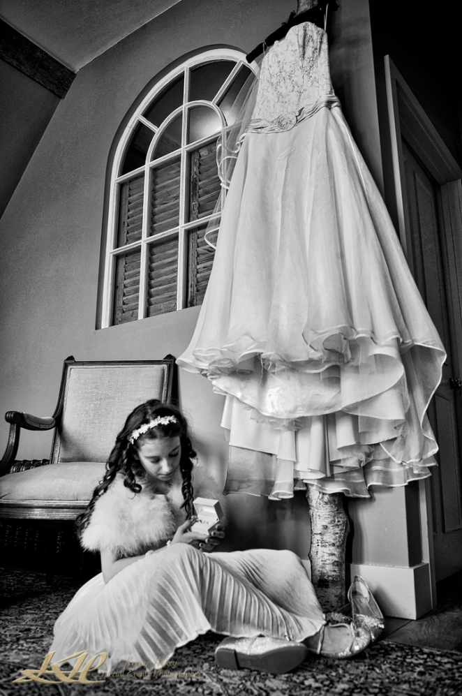 Bridesmaid sitting on floor looking at jewellery with long wedding dress hanging up in black & white