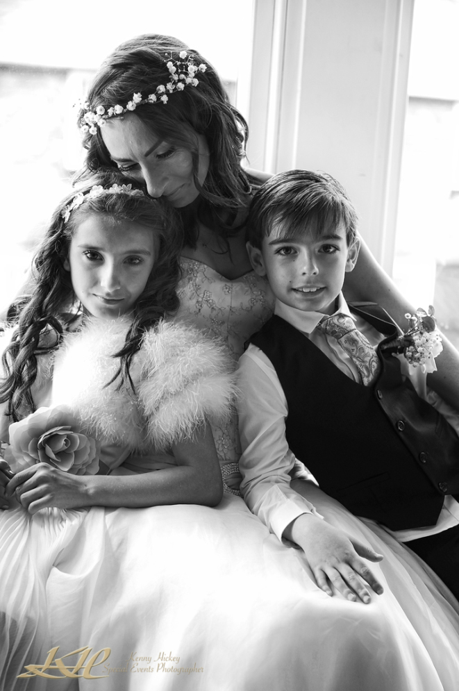 lovely image of bride with son & daughter posing by window in black & white