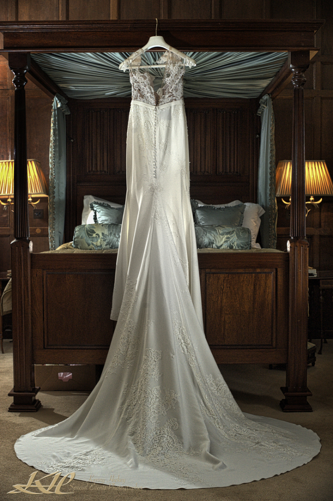 Stunning long wedding dress hanging on four poster bed in Tulip Room at Hever Castle