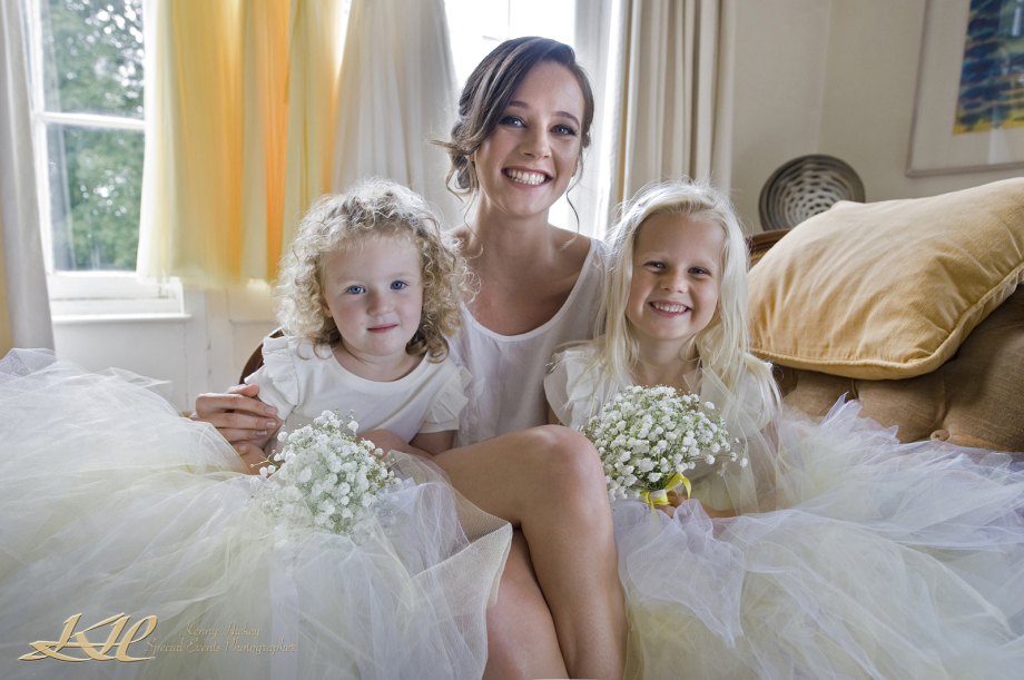beautiful bride sitting on bed with stunning bridesmaids