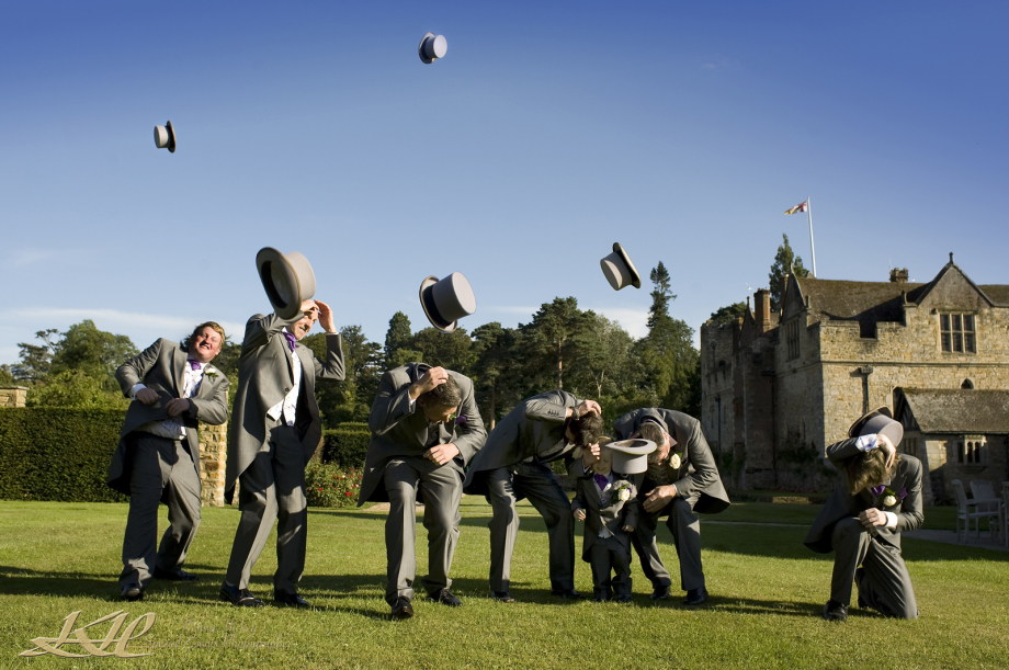 Groom & groomsmen throwing bowler hats in the air at Hever Castle
