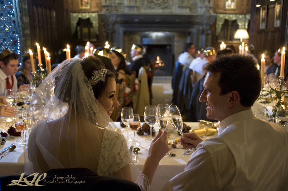 Bride & Groom chinking glasses during Christmas wedding breakfast at Hever Castle