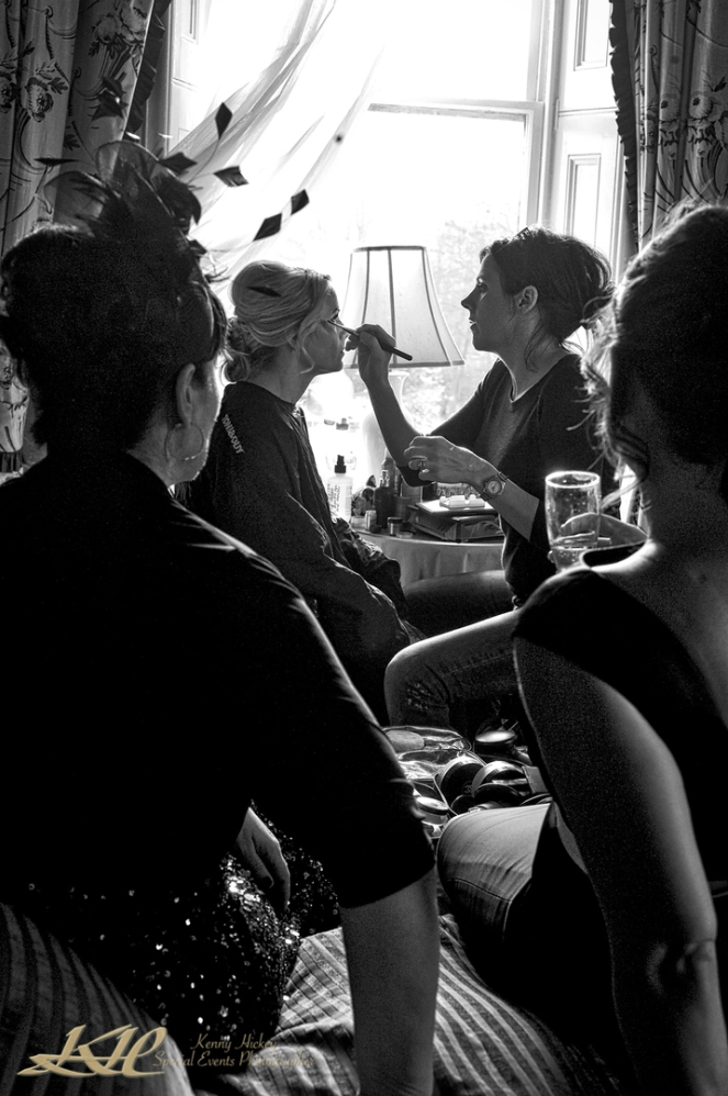 Bride having make-up done with bridesmaids watching in black & white