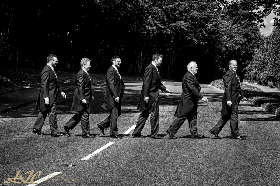 Groom followed by groomsmen walking across main road in a line