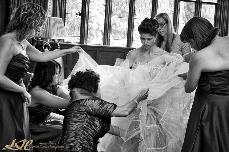 bride with briadla party fixing wedding dress at Hever Castle in black & white