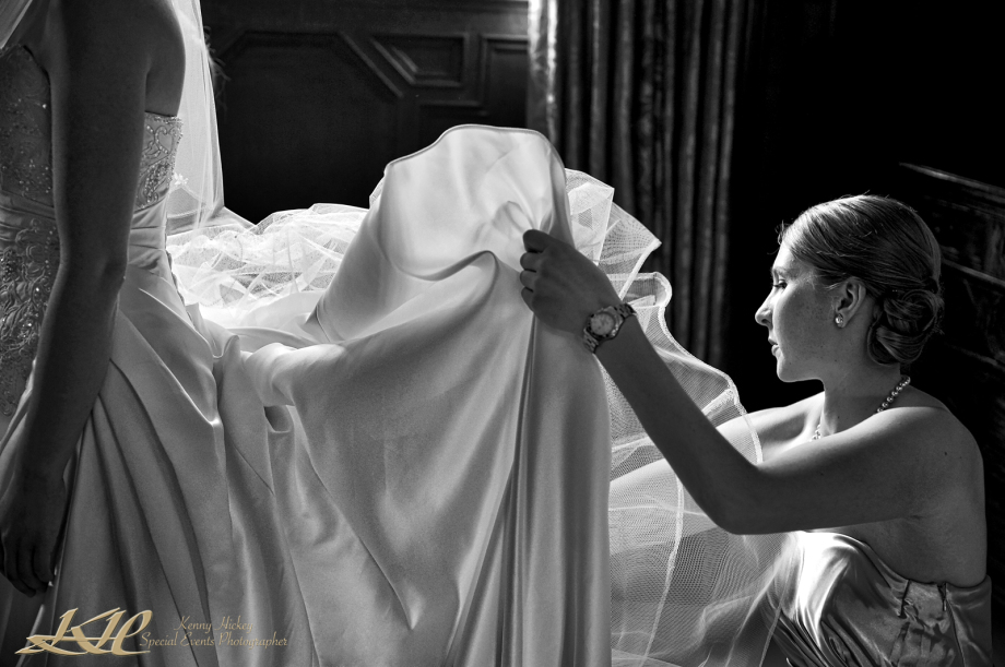 bridesmaid fixing wedding dress for bride in black & white
