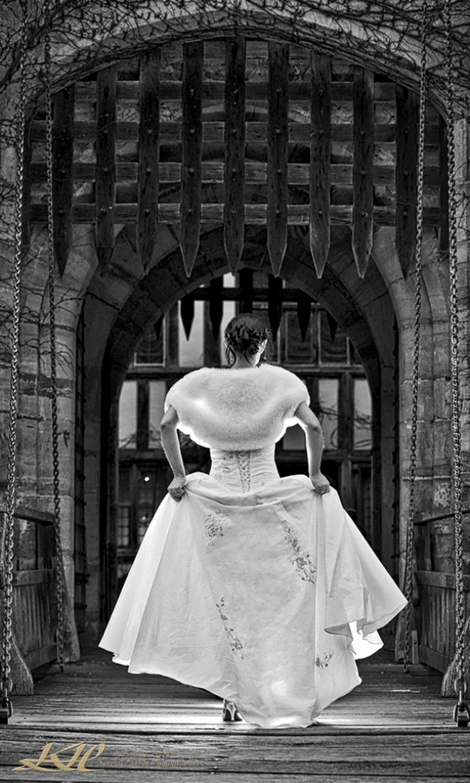 bride in wedding dress walking on drawbridge at Hever castle in black & white