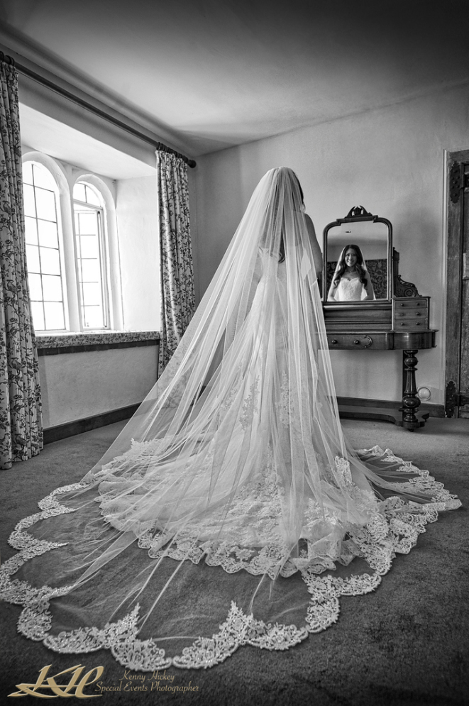 Gorgeous chinese bride in full wedding dress posing by mirror in black & white