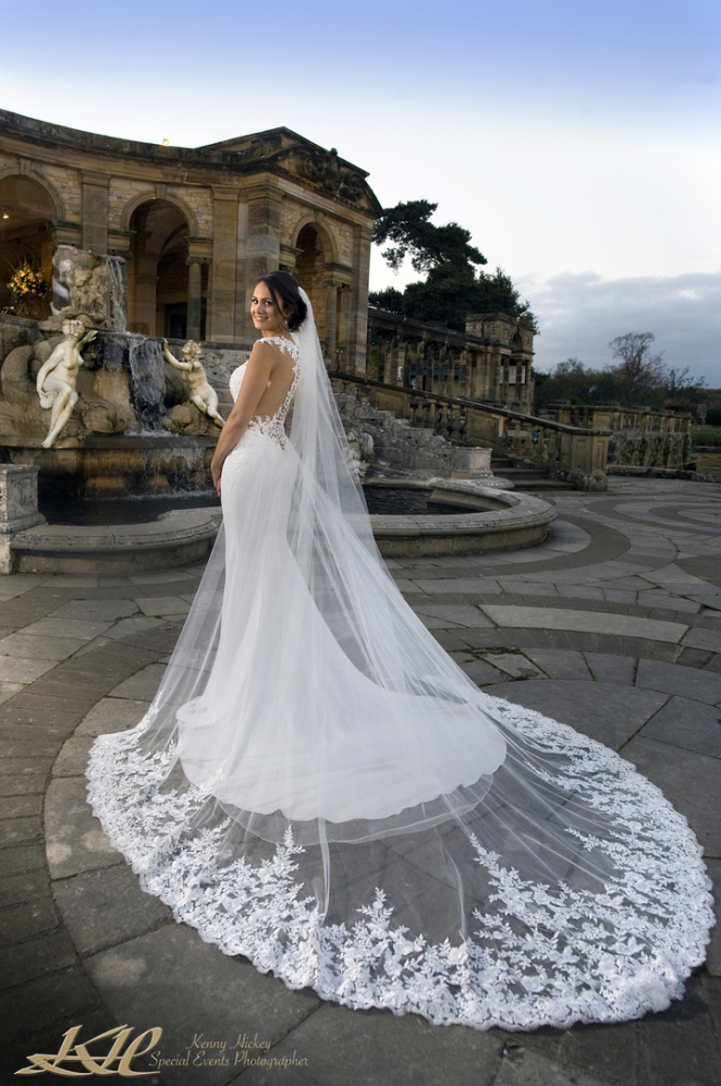 Beautiful bride in full wedding dress posing by the loggia and fountain at Hever castle