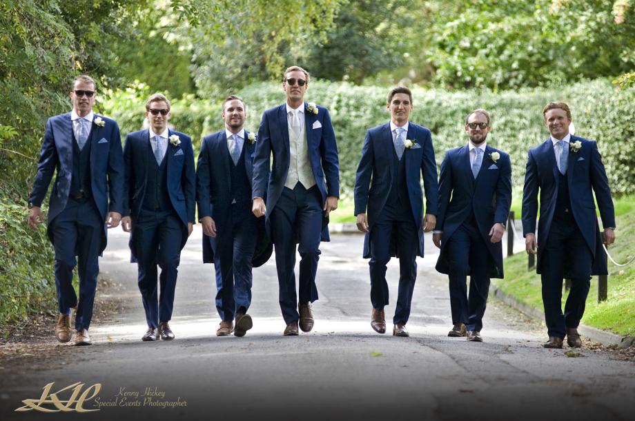 Groom and groomsmen walking to church in blue suits reportage