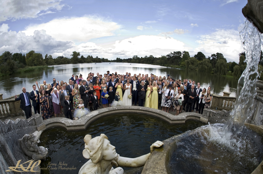 all wedding party posing byHever castle lake with water fountain in foreground
