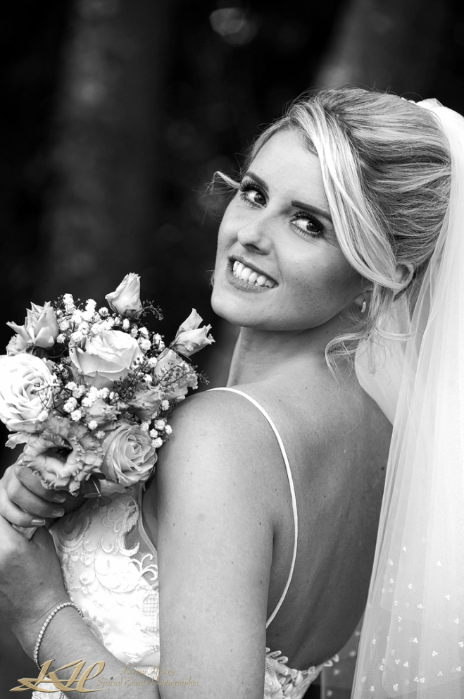 beautiful bride looking back at camera with wedding bouquet in black & white