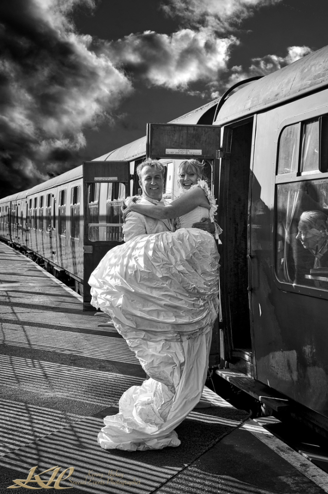 Groom carrying bride onto train at High Rocks in black & white