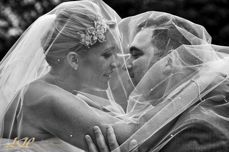 creative black & white looking romantically under wedding veil in black & white
