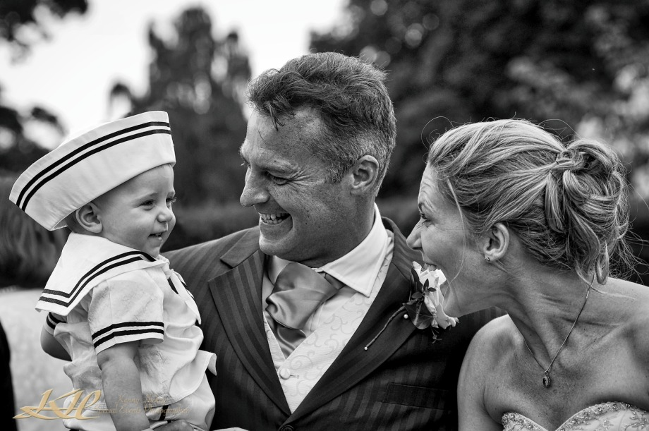 Bride & groom laughing with young son in sailors hat in black & white