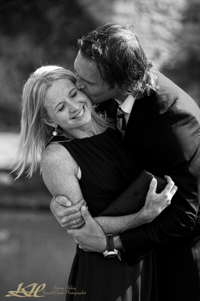 repotage photo of wedding guest kissing girlfriend in black & white