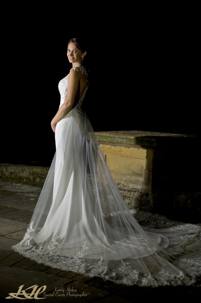 Beautiful Bride in wedding dress posing by lake at night