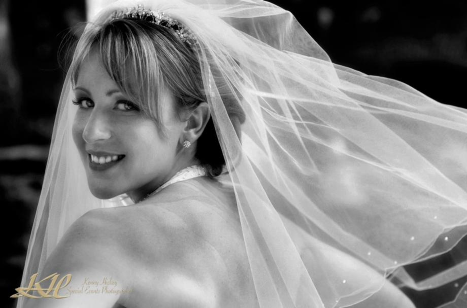 Beautiful smiling bride in flowing veil in black & white