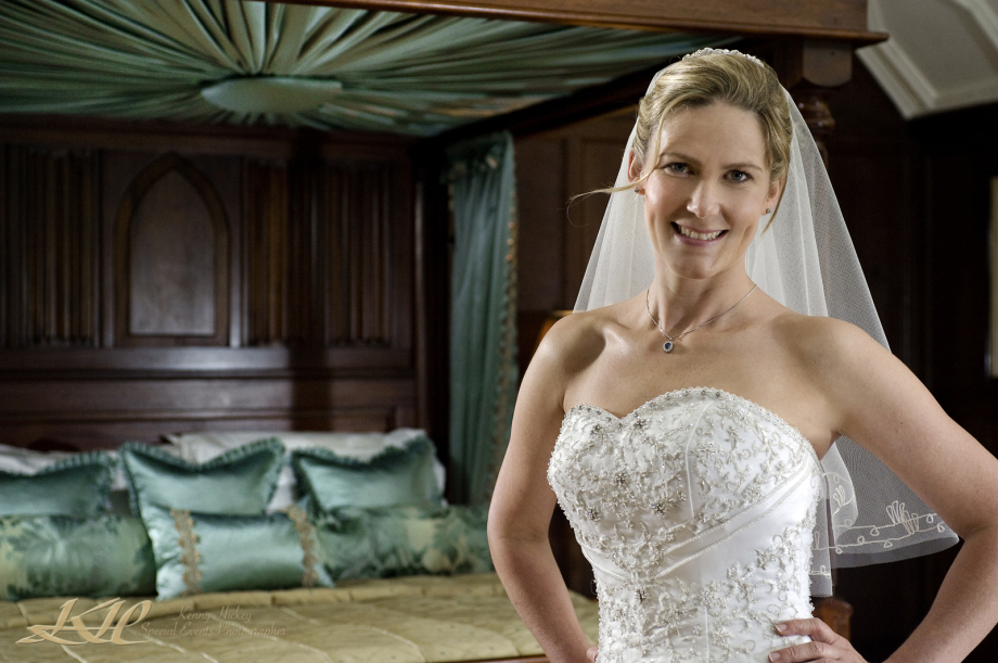 Bride in veil posing by four poster bed at Hever Castle